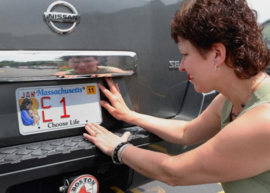 Merry Nordeen, the woman behind the new tags, put the plate on her car.