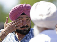 A man wipes away tears outside the Sikh Temple in Oak Creek, Wis. where a shooting took place on Sunday, Aug5,2012. (AP Photo/Jeffrey Phelps)