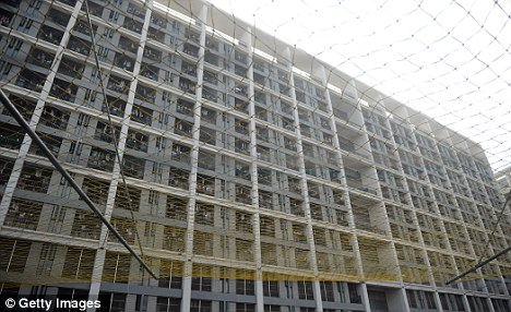 Grim: Netting has been put up outside worker dormitories buildings in Chengdu and Shenzhen after a spate of suicides last year