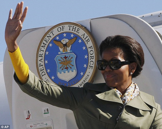 Thanks for the memories: Michelle Obama waves as she boards her private plane after a week-long trip to Africa, which could have cost the taxpayer an estimated $800,000