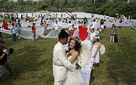 The bride and groom smiling at a wedding held in Jilin, China: Chinese bride gets married in 1.4 mile-long wedding dress