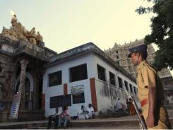An Indian police officer stands guard at the Sree Padmanabhaswamy Temple in Trivandrum, India. A vast treasure trove has been found there.