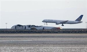 An aircraft lands behind the wreckage of the Asiana Airlines plane at San Francisco International Airport in San Francisco