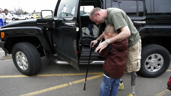 FILE - In this April 7, 2008 file photo, retired Minnesota National Guard Sgt. John Kriesel comforts his son, Broden, 5, outside a mall in Roseville, Minn.Kriesel lost both of his legs in a roadside bomb attack while patrolling near Fallujah, Iraq in December 2006. Veterans of the Iraq War watched in frustration as Republican presidential contenders have distanced themselves from the original decision their party enthusiastically supported to invade that country. Some veterans say they long ago concluded their sacrifice was in vain, and are annoyed that a party that fervently lobbied for the war is now running from it. Other say they still believe their mission was vital, regardless of what the politicians say. And some find the gotcha question being posed to the politicians _ knowing what we know now, would you have invaded? _ an insult in itself. (AP Photo/Jae C. Hong, File)